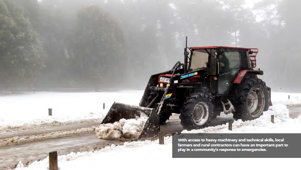A tractor clears snow from a roadway after the Beast From The East Winter Storm.