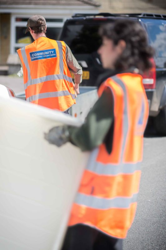 A close-up of two volunteers in front of a car, facing away from the camera. Both volunteers are dressed in high-vis clothing and are carrying boxes.